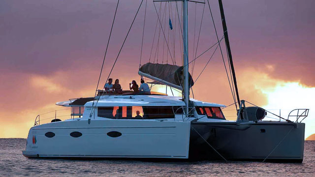 Bareboat sailing catamaran at tropical sunset